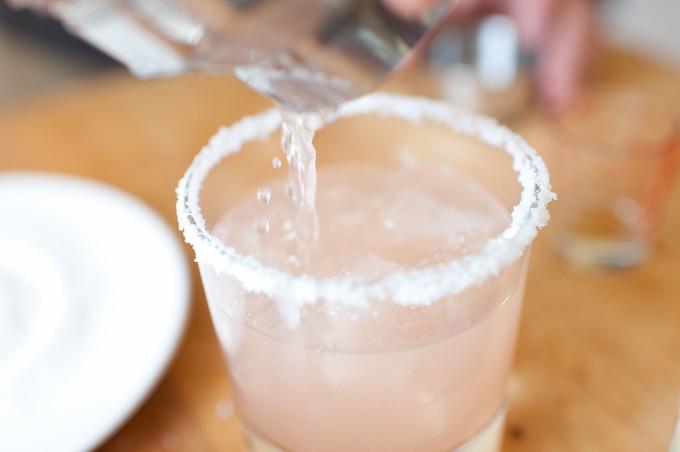pouring margarita into glass